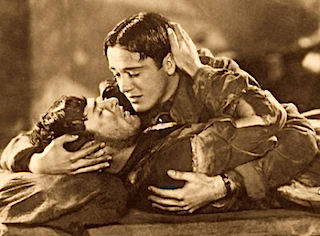 "Richard Arlen and Buddy Rogers share a passionate embrace and onscreen kiss in ""Wings,"" 1927."