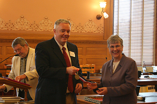 "Paul Miles Schneider receives his medal from Jo Budler, the State Librarian of Kansas, as author of ""Silver Shoes,"" one of the 2010 Kansas Notable Books."