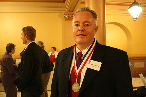 "Paul Miles Schneider proudly wears his medal for ""Silver Shoes"" at the 2010 Kansas Notable Books awards reception."