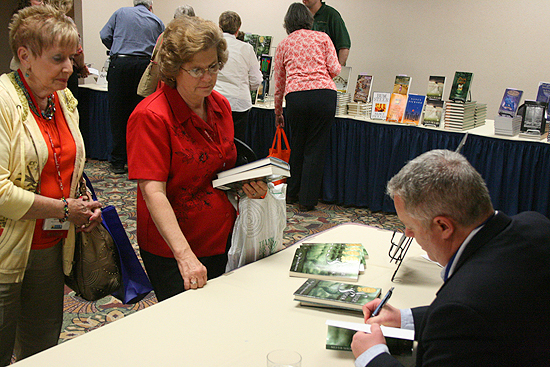 "Paul Miles Schneider signs copies of ""Silver Shoes"" at the Kansas Library Association's annual convention. 2011."