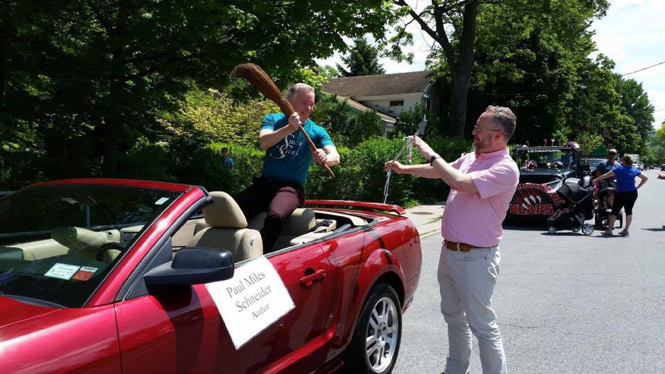"Good vs. Evil at the parade for Oz-Stravaganza 2016, as Paul Miles Schneider and Grant Menzies battle with a wand and broom. All in good fun. Authors of ""Silver Shoes"" and ""Mrs. Ziegfeld,"" respectively."