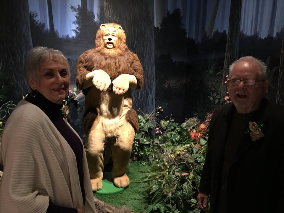 "Two ""Oz treasures"" pose in the Oz Museum next to the Cowardly Lion's display in Wamego, KS, 2016. Charlene Baum, and L. Frank Baum's great-grandson Roger S. Baum."